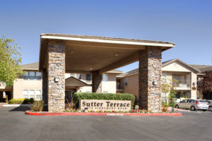Sutter Terrace sign with large covered stone front entrance drive through in parking lot